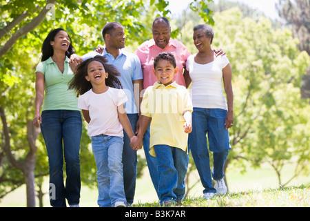Großfamilie zu Fuß im Park Hand in Hand und lächelt - Stockfoto