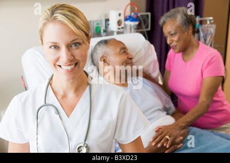 Arzt sucht fröhlich im Krankenzimmer - Stockfoto