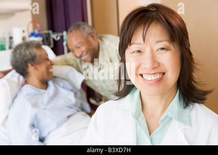 Krankenschwester, die lächelnd im Krankenzimmer - Stockfoto