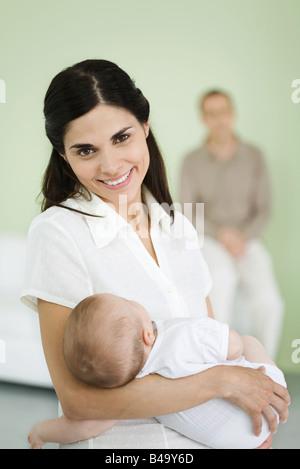 Mutter Baby halten, lächelnd in die Kamera, Mann im Hintergrund - Stockfoto