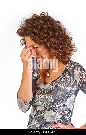Die Brücke der Nase mit geschlossenen Augen kneifen zeigt eine Stimmung negativer Bewertung in dieser Frau - Stockfoto