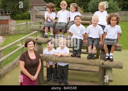 Studenten sitzen im Freien auf Holzkonstruktion mit Lehrer, die neben ihnen stehenden - Stockfoto
