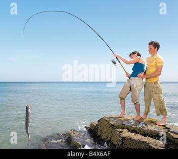Paar Landung ein großer Fisch aus Felsen - Stockfoto