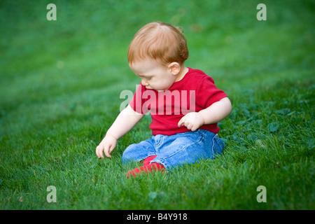 Junge rothaarige junge draußen auf dem Rasen sitzen - Stockfoto