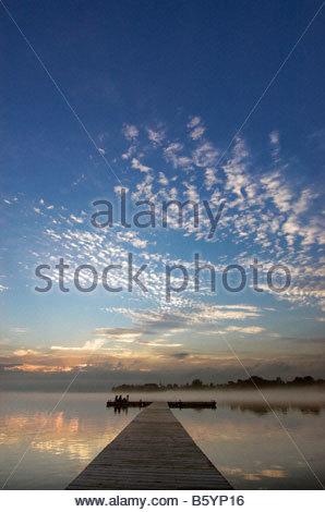 Drei junge Mädchen sitzen am Ende eines Piers bei Sonnenuntergang - Stockfoto