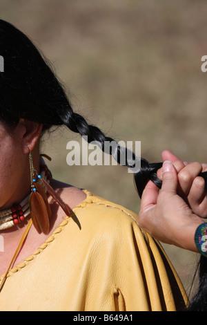 Zwei Native American Indian Frauen mit Fransen Lederkleid Eachother Zöpfe flechten - Stockfoto