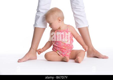 Babymädchen sitzen zwischen den Füßen der Mütter - Stockfoto