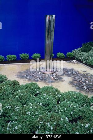 Spiegel-Obelisk in einen flachen Pool Silhouette gegen eine blaue Wand - Stockfoto