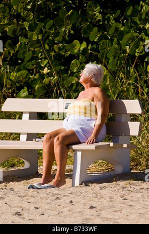 Palm Beach Shores, Florida, Reife große grauen Haaren Seniorin schlafend im Sonne Sonnenbaden auf Bank auf Sand - Stockfoto