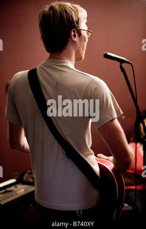 Junger Mann Gitarre spielen und singen in Mikrofon - Stockfoto