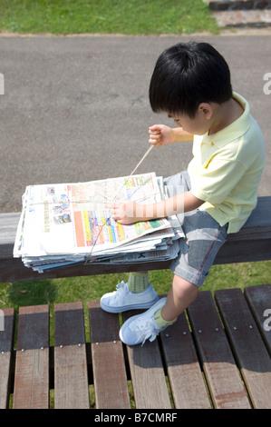Kleiner Junge sitzt auf der Bank und binden nespaper - Stockfoto