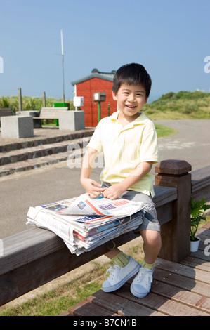 Kleiner Junge sitzt auf der Bank mit Zeitung - Stockfoto