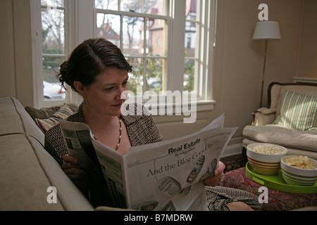 Eine Frau sitzt in ihrem Wohnzimmer den Immobilienbereich der New York Times zu lesen. - Stockfoto
