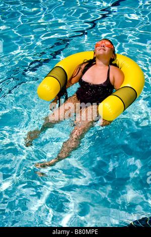 Tragen von Schutzbrillen, die ein Zehn Jahres altes Mädchen schwebt in einem Schwimmbad in Laguna Niguel CA - Stockfoto