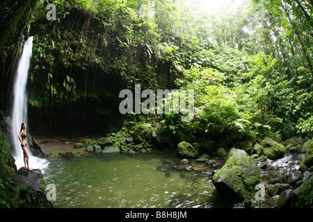 Frau stehend im Emerald Pool Wasserfall im Dschungel des Morne Trois Pitons National Park auf der karibischen Insel - Stockfoto
