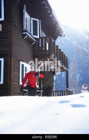 Paar vor Chalet mit ihrem ski - Stockfoto