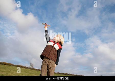 Junge mit Spielflugzeug in Landschaft - Stockfoto