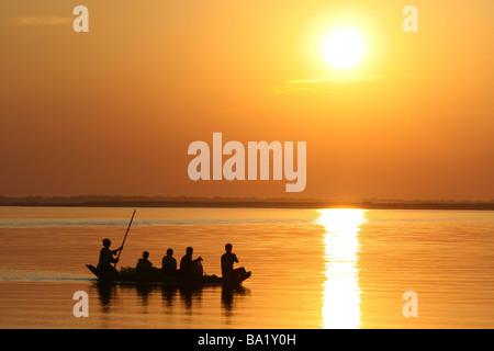 Angelboot/Fischerboot bei Sonnenuntergang am Fluss Brahmaputra, Assam, Indien - Stockfoto