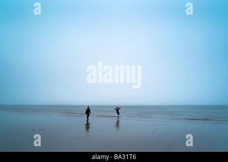 Zwei Personen spielen an einem Strand im Südosten Englands, an einem nebligen Tag im Frühling - Stockfoto