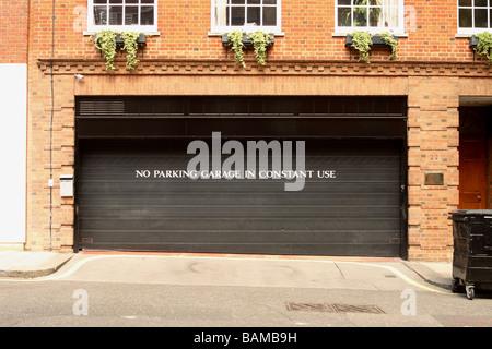 London No Parking Garage im Dauereinsatz Warnschild am Privatgarage Eingangstüren in exklusiven Mayfair London - Stockfoto