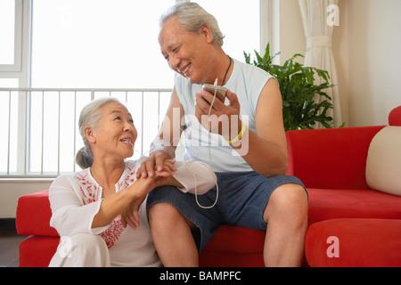 Älteres Ehepaar zusammen anhören von MP3-Player - Stockfoto
