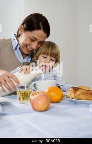 Eine Mutter ihren Sohn Gießen Milch helfen - Stockfoto