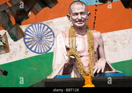 Die bekränzten Statue von Mahatma Gandhi steht vor der indischen Flagge. - Stockfoto