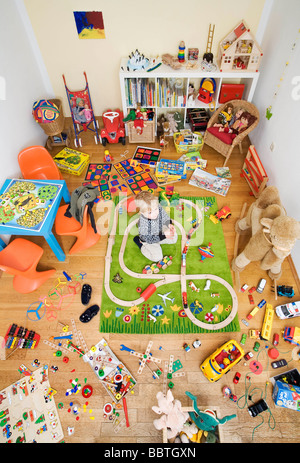 Junge spielt im Zimmer voll mit Spielzeug - Stockfoto