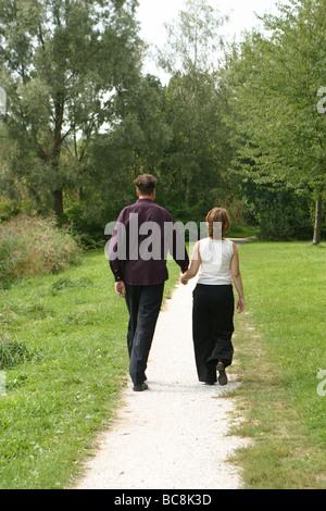 Zurück Blick anonym paar und zu Fuß Routine im Park, die Hand in Hand, dritten Trimenon der Schwangerschaft - Stockfoto