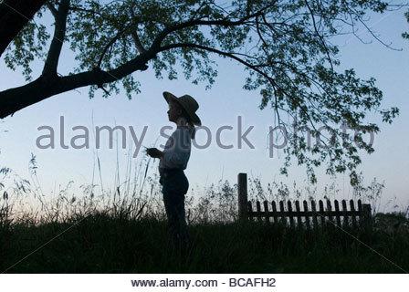 Ein junges Mädchen ist Silhouette gegen den Himmel auf einem Bauernhof. - Stockfoto
