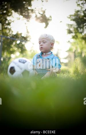 Jungen spielen im Freien mit einem Fußball - Stockfoto