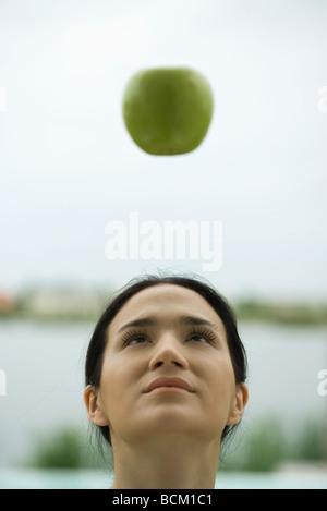 Frau, die bei Apple, die schwebend in der Luft, Vorderansicht - Stockfoto