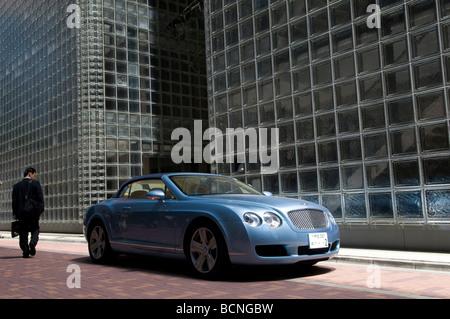 Ein Japaner vorbei ein Bentley-Auto vor Maison Hermes Gebäude im Ginza-Viertel Tokio Japan - Stockfoto