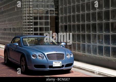 Eine japanische Frau spricht mit einem Fahrer in einem Bentley Auto vor Maison Hermes Gebäude im Ginza-Viertel Tokio - Stockfoto