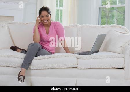 Geschäftsfrau, die sitzen auf der Couch mit einem laptop - Stockfoto