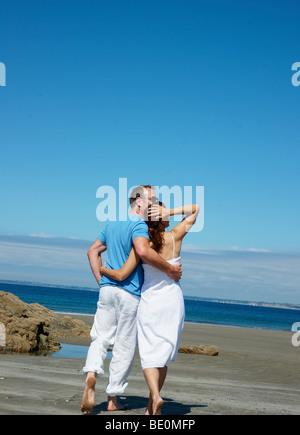Paar, gehen Arm in Arm auf dem Strand und Blick auf das Meer - Stockfoto