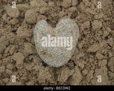 Herz von Stein liegen im nassen sand - Stockfoto