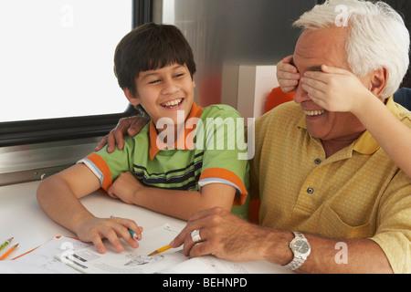 Senior woman hilft seinem Enkel in seine Hausaufgaben und Hände des Kindes für seine Augen von hinten - Stockfoto