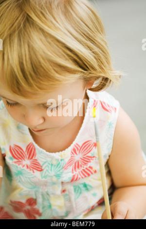 Kleinkind Mädchen hält Pinsel, Blick nach unten - Stockfoto