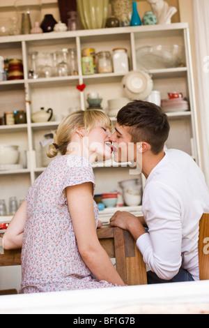 Ein junges Paar küssen mit einer Erdbeere - Stockfoto