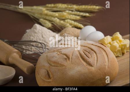 Nahaufnahme von einem Laib Brot mit Eiern auf ein Schneidebrett - Stockfoto