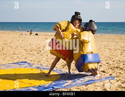 Zwei Jugendliche in Sumo-Ringen Spaß Kostüme gekleidet. Sonnigen Tag am Strand von Bournemouth. Dorset. UK - Stockfoto