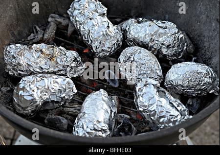 Eingewickelt in Alufolie auf dem Grill Backen Kartoffeln - Stockfoto