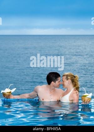 schöne Kaukasischen Paare genießen ihren Urlaub in einem schönen Swimmingpool am Meer - Stockfoto