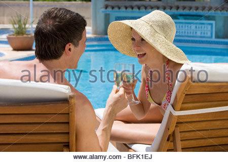 Paar auf Liegestühlen Toasten Sektgläser am Pool - Stockfoto
