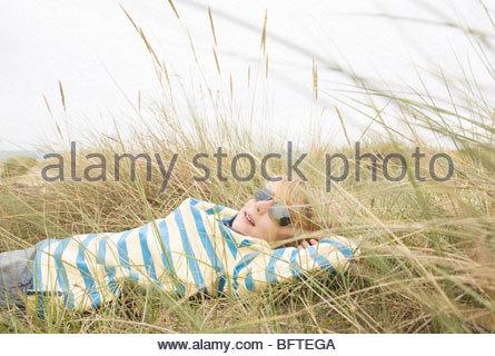 Junge liegend mit Sonnenbrille in Dünen - Stockfoto