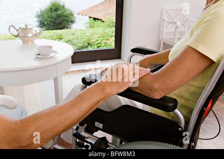 Mann, die Frau im Rollstuhl zu berühren - Stockfoto