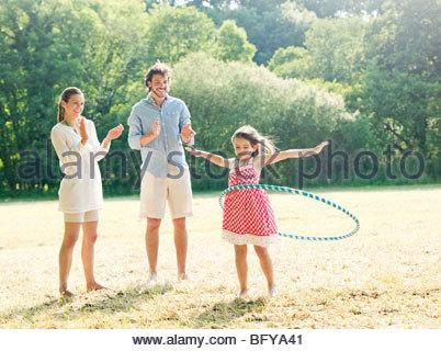 Familie spielt mit dem Reifen im Feld - Stockfoto