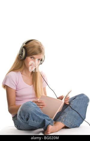 Teenager-Mädchen sitzen mit gekreuzten Beinen Buch lesen und hören Musik isoliert auf weißem Hintergrund - Stockfoto