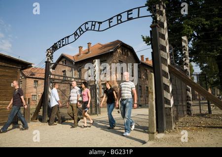 Touristen am Haupteingang – mit echter Arbeit Macht Frei Slogan vor den Toren – Auschwitz Nazi-Camp in Oswiecim, - Stockfoto